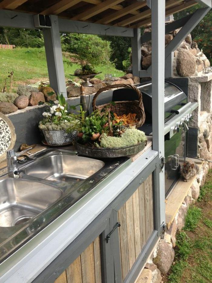 une cuisine d'extérieure rustique équipé d'un barbecue, construction en pierre et en bois
