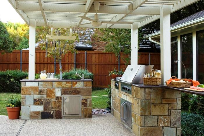 cuisine d'été aménagée sous un pergola en bois blanc, construction solide en pierre naturelle