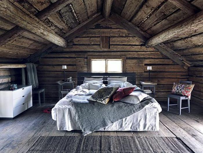 déco chambre sous pente, revêtement sol, toiture en bois brut, linge de lit blanc, couverture de lit grise, coussins multicolores, commode blanc, tapis gris, style rustique