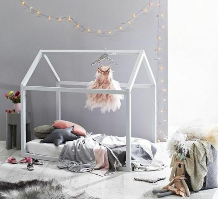 pédagogie montessori, lit maisonnette blanc, matelas, coussins, linge de lit blanc, gris et rose, peinture murale grise, revêtement sol parquet blanc et gris, tapis blanc et gris