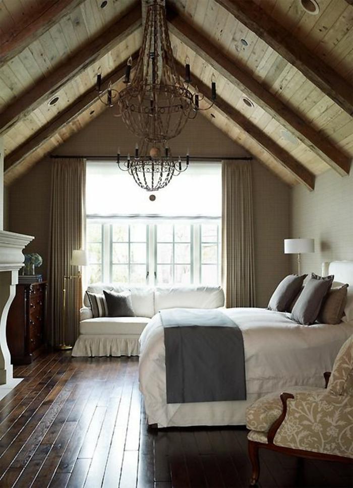 amenager comble. parquet en bois, lit, linge de lit blanc, coussins et couverture de lit gris, canapé blanc, suspension vintage, cheminée toiture mansardée en bois