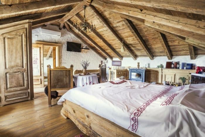 amenagement comble, parquet en bois clair, charpente en bois toiture, lit en bois rustique, porte en bois, mobilier en bois, linge de lit blanc, motifs ethniques