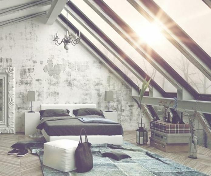 déco chambre sous pente, tapis bleu et vert, parquet, chambre loft, lit blanc, linge de lit gris, mur usé, table, composée de trois malles vintage superposées, fenêtres de toit, lustre, grand miroir