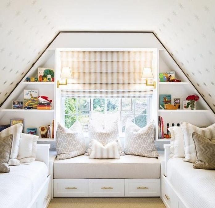 déco chambre sous pente, deux lits, linge de lit blanc, coussins, étagères, jouets, banquette sous la fenêtre avec des tiroirs