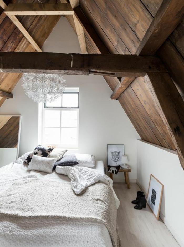 chambre mansardée, comble aménagé en chambre style scandinave, linge de lit blanc, miroir, coussins en noir et blanc, deco suspendue, toiture en bois