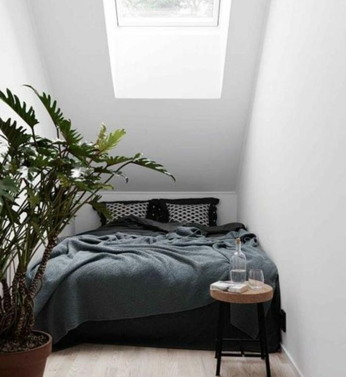 amenagement comble, lit, linge de lit en noir et gris, coussins en noir et blanc, plante, table de nuit, tabouret en métal et bois, parquet clair