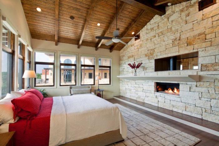 mur d accent en pierres avec cheminée intégrée, amenagemenc combles, chambre à coucher romantique, lit en bois, linge de lit en blanc et rouge, tapis beige, toit mansardé en bois