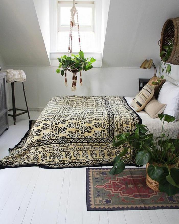 déco chambre sous pente exotique, ling de lit blanc, couverture de lit à motifs orientaux, parquet blanc, plantes suspendues vertes, tapis oriental
