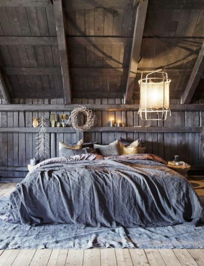 déco chambre style rustique, crèche, amenanger comble, linge de lit gris, coussins multicolores, suspension design, parquet clair, mur et toit mansardé bois brut