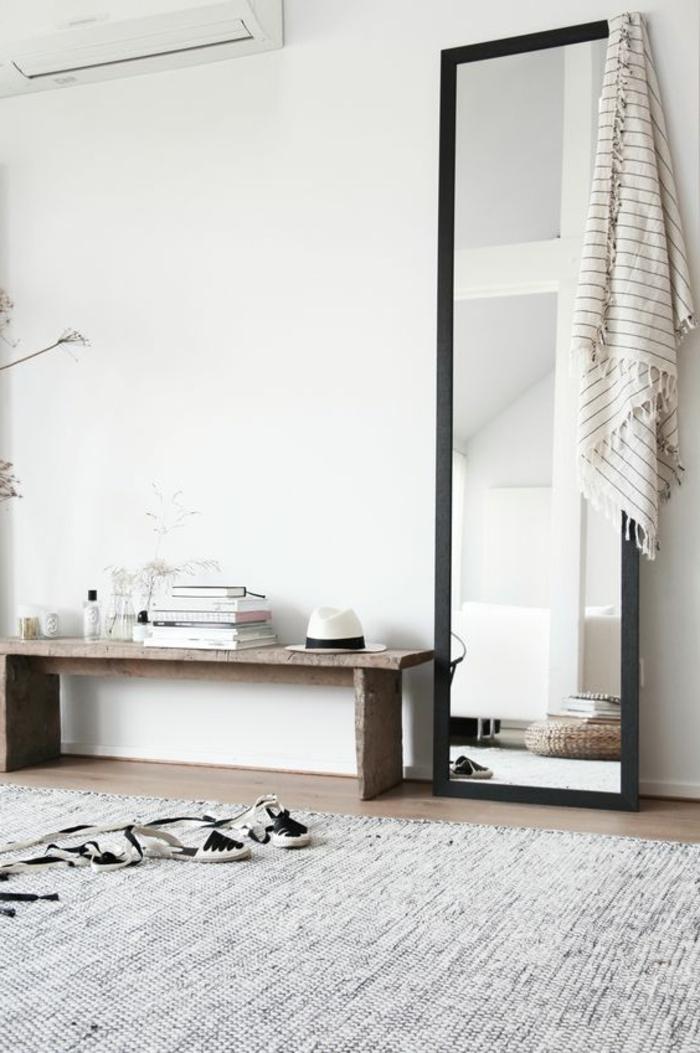 déco minimaliste, grand miroir rectangulaire et une banquette en bois