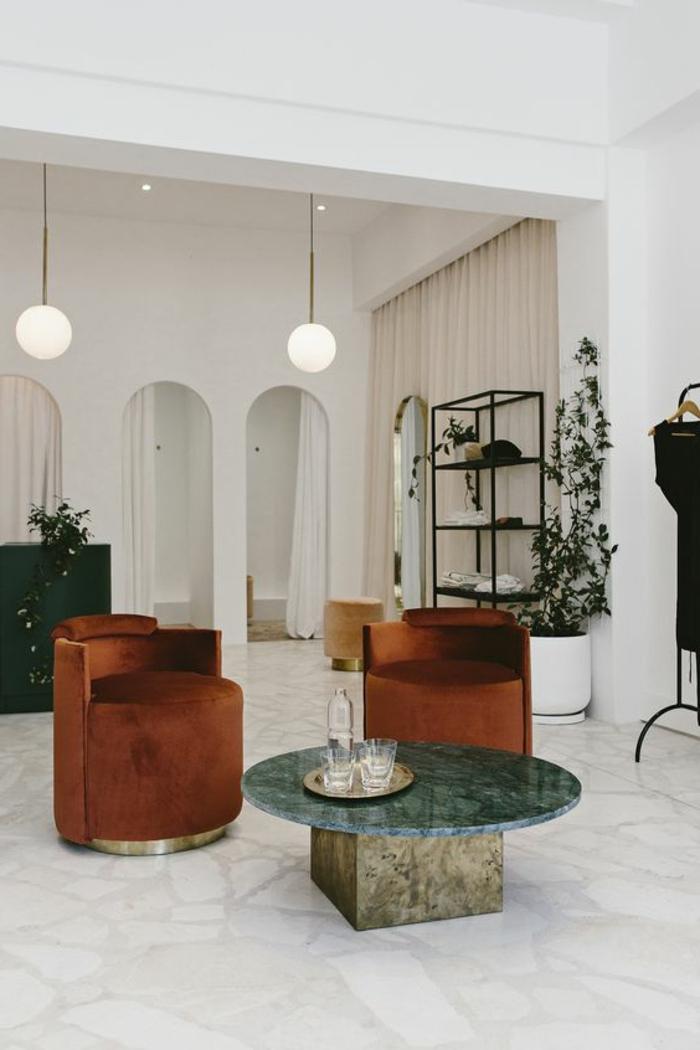 déco minimaliste, étagère métallique, lampes suspendues rondes et deux fauteuils ronds