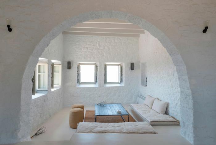 meuble en pierre grec, murs blanchis à la chaux, volets kaki, table basse en bois