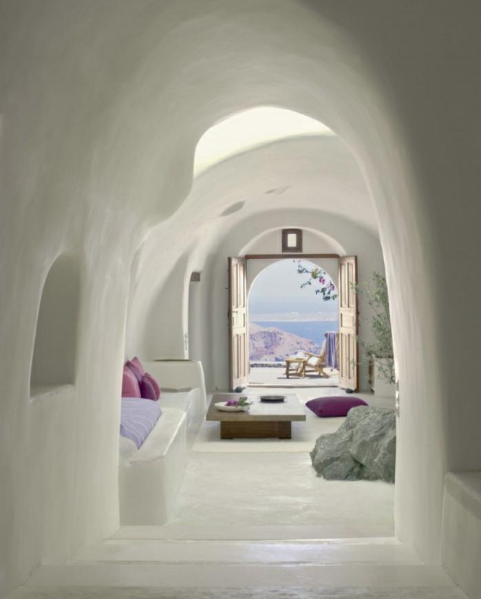 meuble en pierre grec, arc, portailles vers la terrasse, table basse en bois