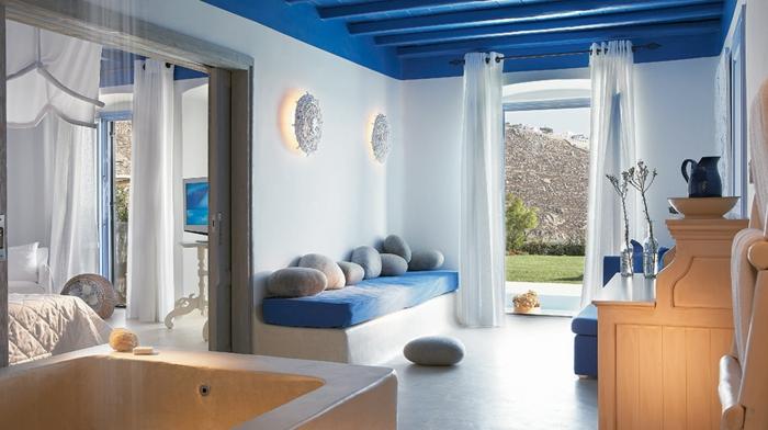 bleu grec sur le plafond, rideaux blancs, vue sur le jardin, vase antique, coussins imitation pierre