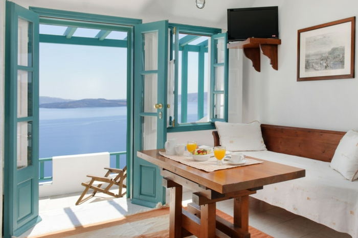 repas grec, volets en turquoise, vue sur la mer, canapé et table en bois
