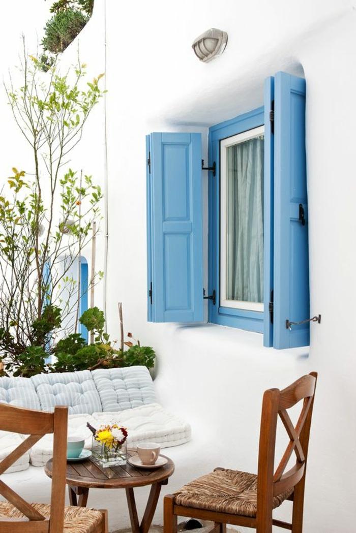 bleu grec sur les volets, salon de jardin en bois, fleurs vertes, façade blanche