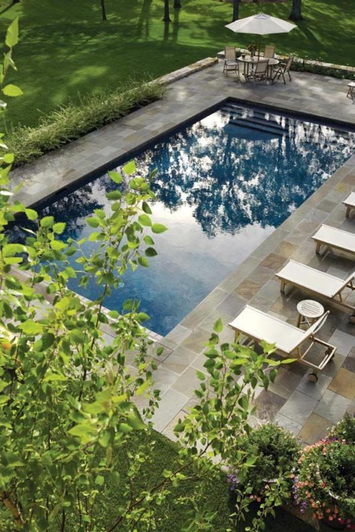 contraste entre le revêtement de la piscine en carrelage et l'entourage piscine en pierre de travertin