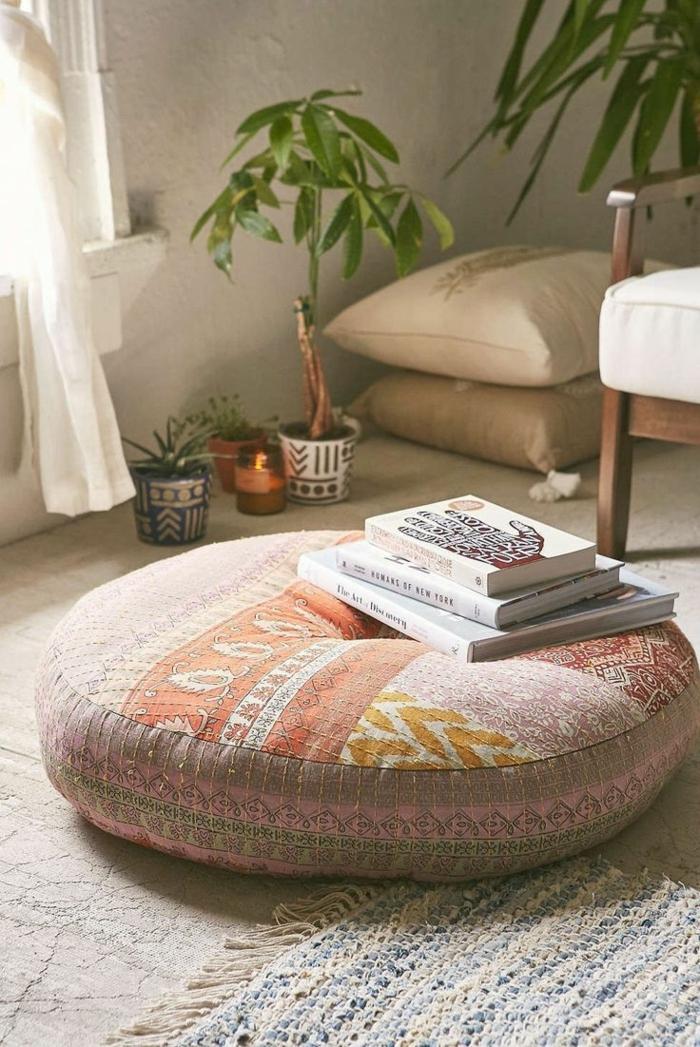 salon boheme, tabouret beige, livres, plantes vertes, tapis avec franges
