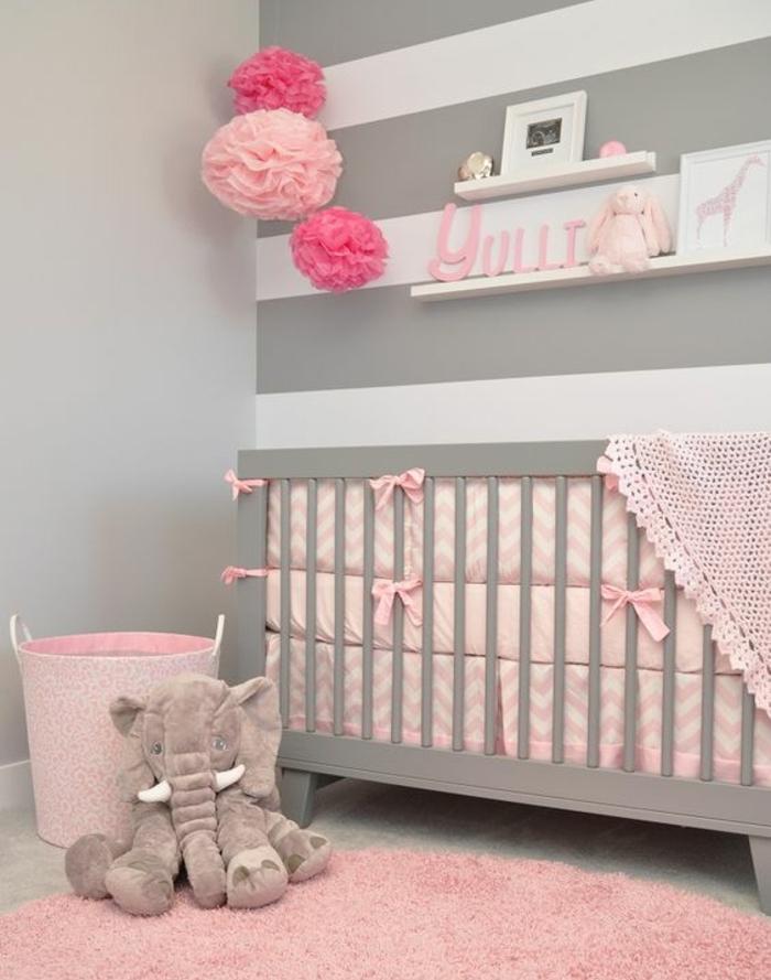 mur couleur grise et mur blanc à rayures grises, lit bébé gris, tour de lit rose et tapis rose, fleurs en papier de soie rose, chambre rose et gris bébé