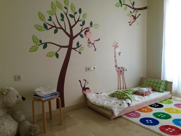 lit en bois à même le sol, stickers chambre enfant arbres, singes, tapis à boutons multicolores, peluche ours, idée lit bébé montessori