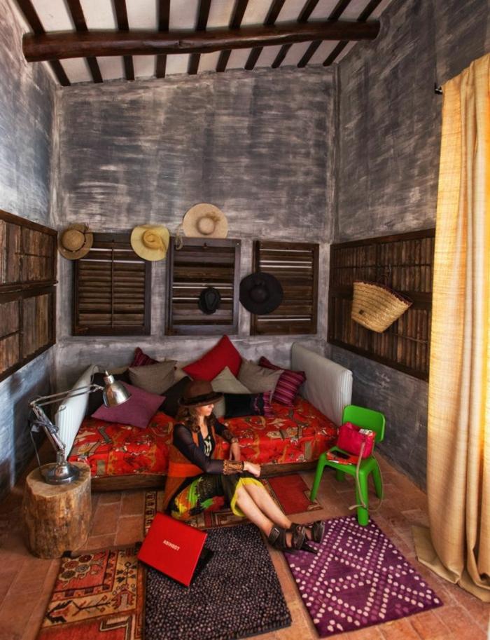 chambre hippie, plafond avec poutres en bois, canapé rouge, tapis ethniques
