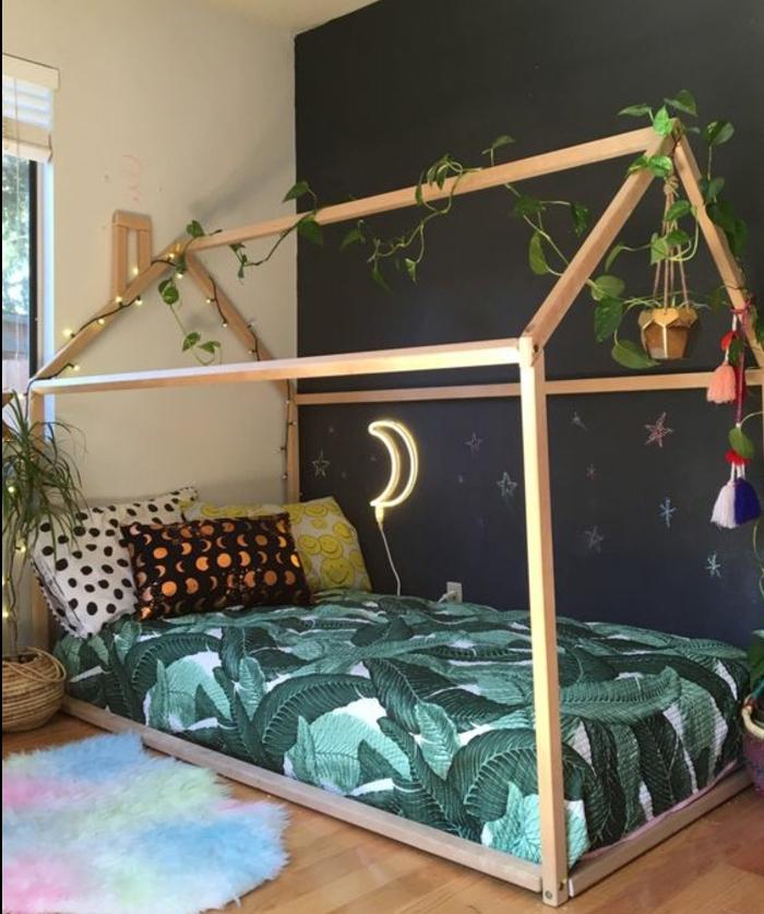 pédagogie montessori, aménagement chambre bébé, lit maisonnette en bois, matelas, oreillers multicolores, mur d accent noir, tapis à plusieurs nuances, guirlande lumineuse