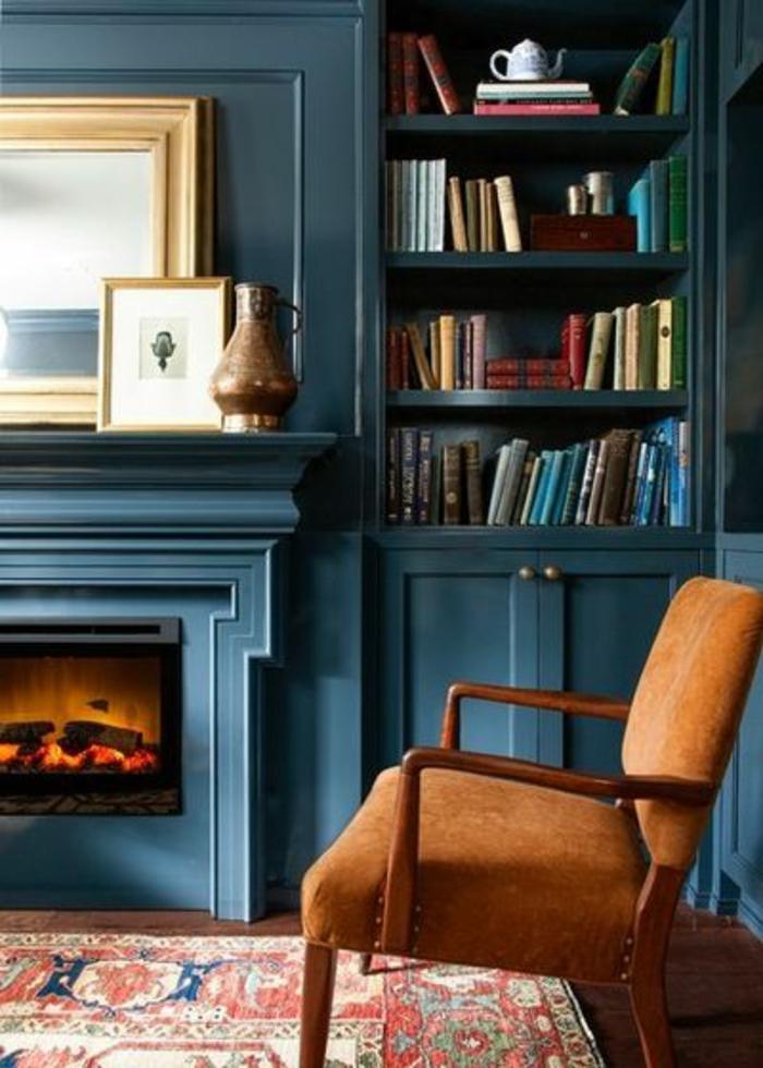 deco salon bleu canard, bibliothèque bleue avec cheminée murale, fauteuil couleur ocre