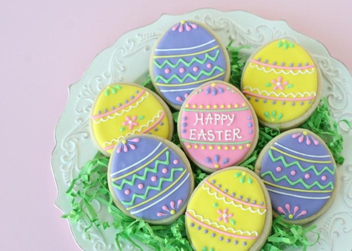 sablés de paques en forme d oeufs décorés multicolores, motifs géométriques, texte joyeuses paques, recette de paques facile