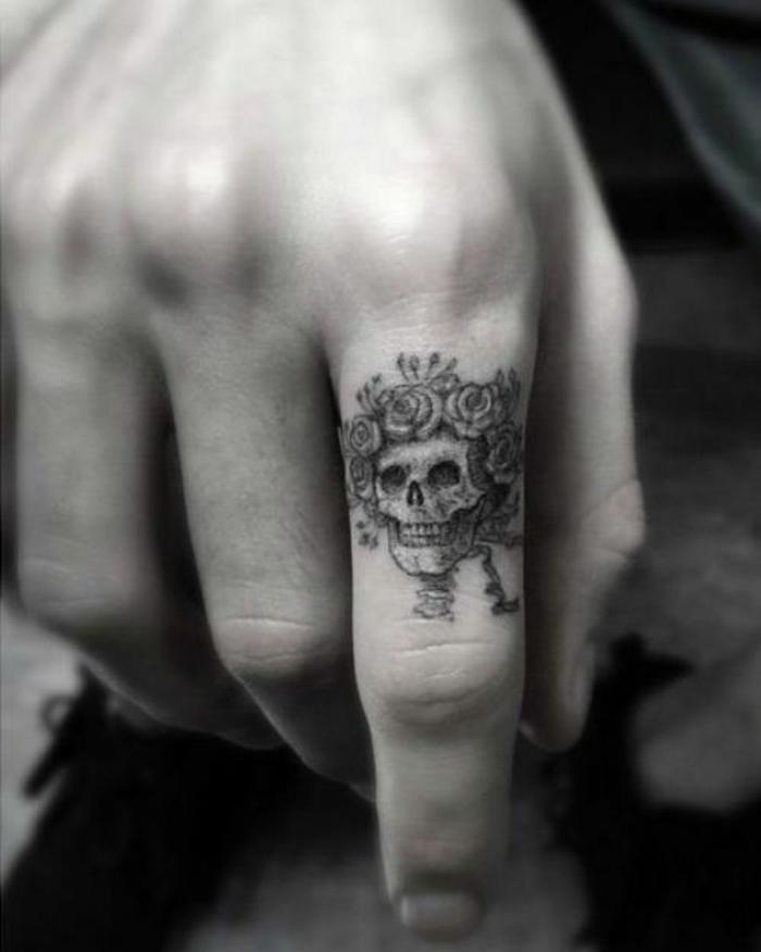 un tatouage doigt homme à tête de mort et roses, un joli dessin à encre graphique