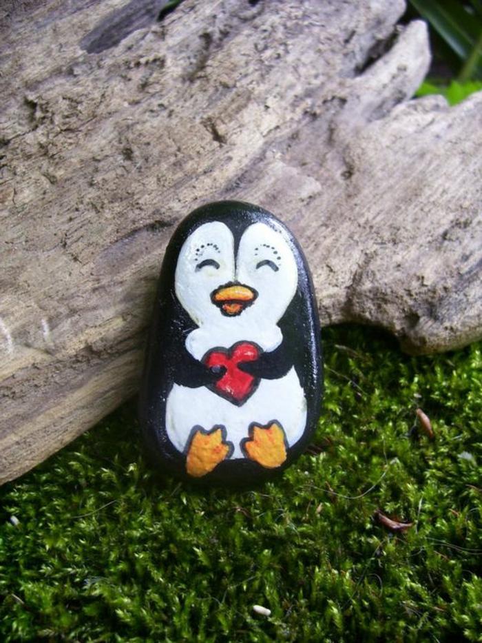 dessin sur galet, pingwin qui tient un coeur, déco de jardin avec pierres et bois fllotté