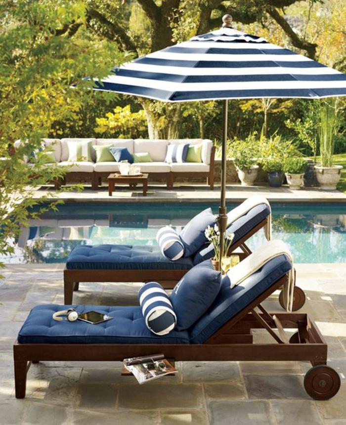 des transats en bleu marin et blanc, decoration moderne autour de la piscine, plage de piscine en pierre