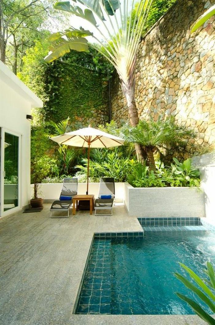jolie piscine verte dans une ambiance tropicale, entourage piscine en pierre