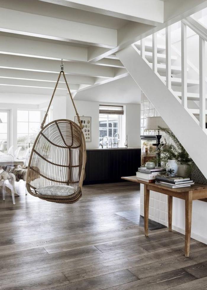 fauteuil balancelle, maison blanche avec escalier blanc et table en bois sous l'escalier