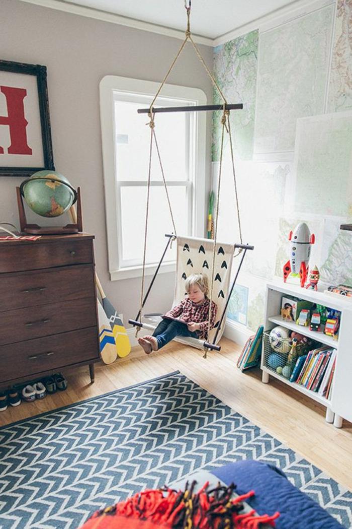 fauteuil balancelle, tapis bleu, étagères basses blanches, globe terrestre, commode en bois