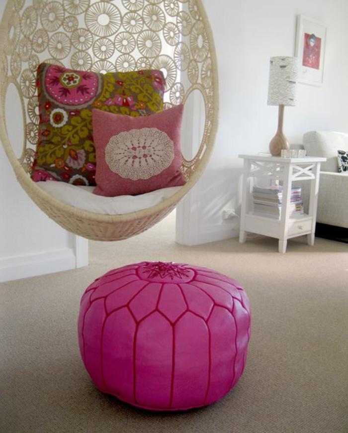fauteuil oeuf suspendu blanc, coussins bariolés, pouf rose, table blanche