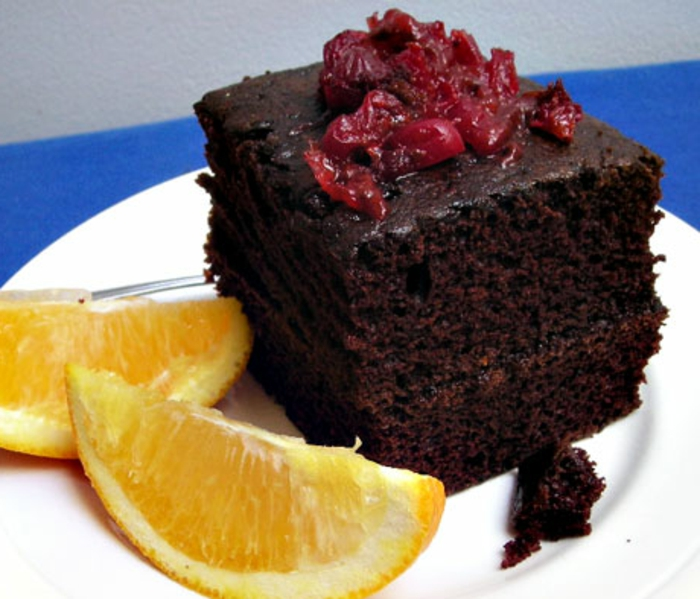 gateau au chocolat sans oeuf, cerises rouges au top et deux tranches de citron