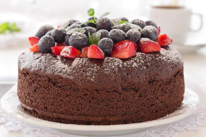 gateau sans oeuf, tarte noire garnie de fraises, myrtilles et feuilles de menthe