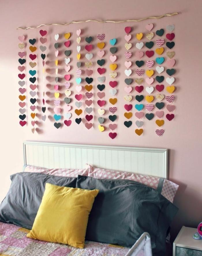 guirlande de papier au dessus d un lit, des coeurs en papier multicolores, suspendus, lit blanc, coussins rose, jaunes et gris, peinture murale rose, idee creation deco, décorer sa chambre