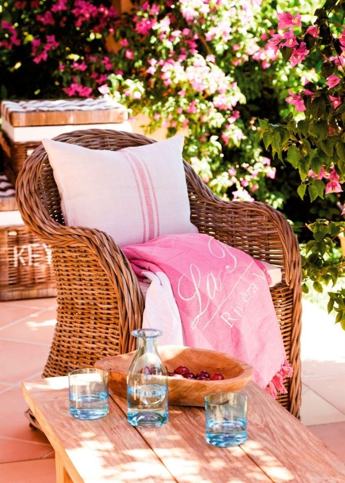 home staging expert, coussin en rose pastel, fauteuil en rotin, plaid en rose foncé avec franges, déco jardin