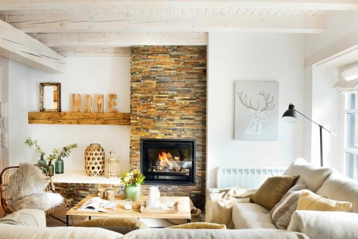 home staging conseils, plafond peint blanc avec poutres en bois, cheminée en pierre, coussins en faux fur