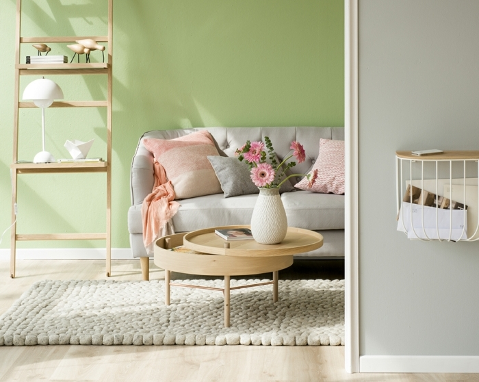 home staging expert, échelle décorative en bois, murs en vert pâle, plaid en orange pastel, table ronde multifonctionne