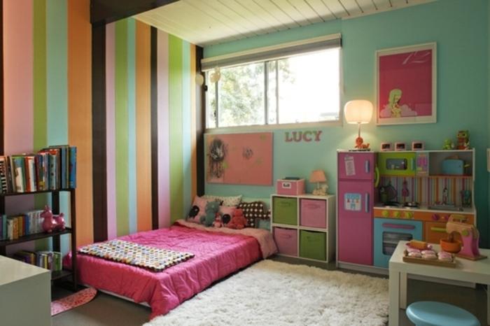 mur couleur verte, et mur d accent à rayures multicolores, lit au sol, couverture de lit rose, tapis blanc cassé, bibliothèque livres, petite cuisine enfant, rangements, chambre montessori fille