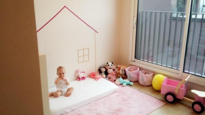 méthode montessori amenagement, matelas blanc, tapis rose, jouets, bacs à jouets, mur couleur ivoire, dessin mur maison