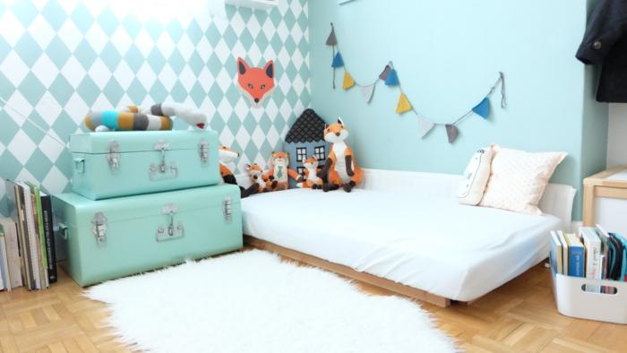 lit bébé montessori, parquet clair, matelas blanc, table de nuit malles vert clair, tapis blanc, peinture murale vert clair et mur d accent vert clair à motifs géométriques blancs, jouets renard