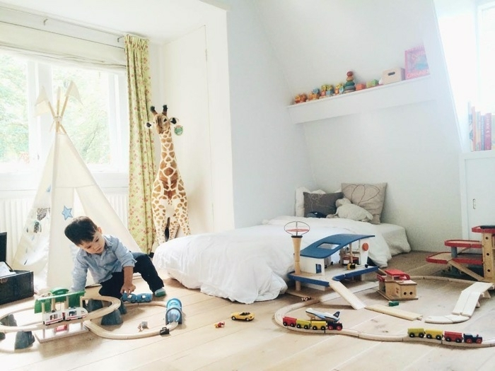 pédagogie montessori aménagement chambre enfant, parquet clair, tipi enfant, déco chambre garcon, tapis matelas sol, peluche girafe, etagere rangement jouets