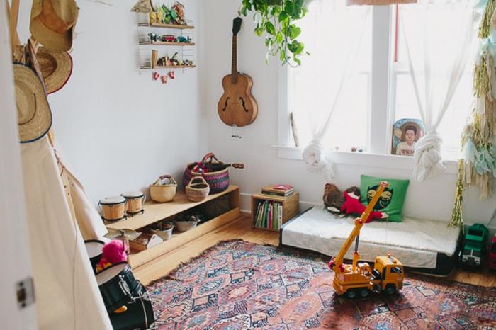 idée comment aménager une chambre montessori, tapis oriental, matelas à même le sol, mur couleur blanche, guitare, rangement bas en bois