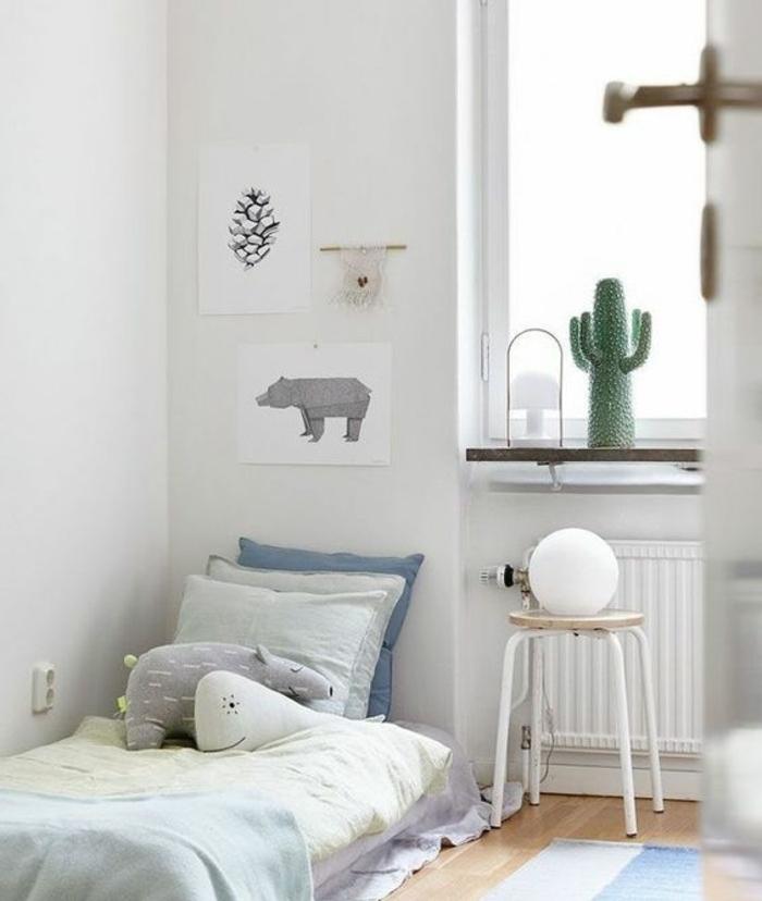 lit bébé montessori, parquet clair, matelas, linge de lit coussins multicolores, table de nuit tabouret, couleur mur blanc, dessins