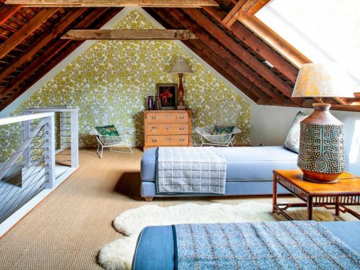 chambre mansardée, mur d accent papier peint à motif points, deux lits bleus, table de nuit en bois, lampe de chevet, motif orientaux, tapis blanc, commode en bois vintage, toit mansardé, charpente bois