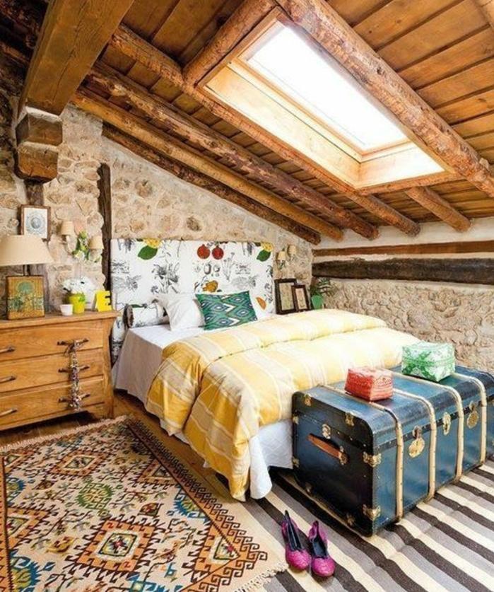 murs en pierre, lit et tête de lit multicolore, tapis à rayures, bout de lit malle bleu, tapis oriental, commode en bois vintage, couverture de lit jaune, poutres apparentes, amenager comble