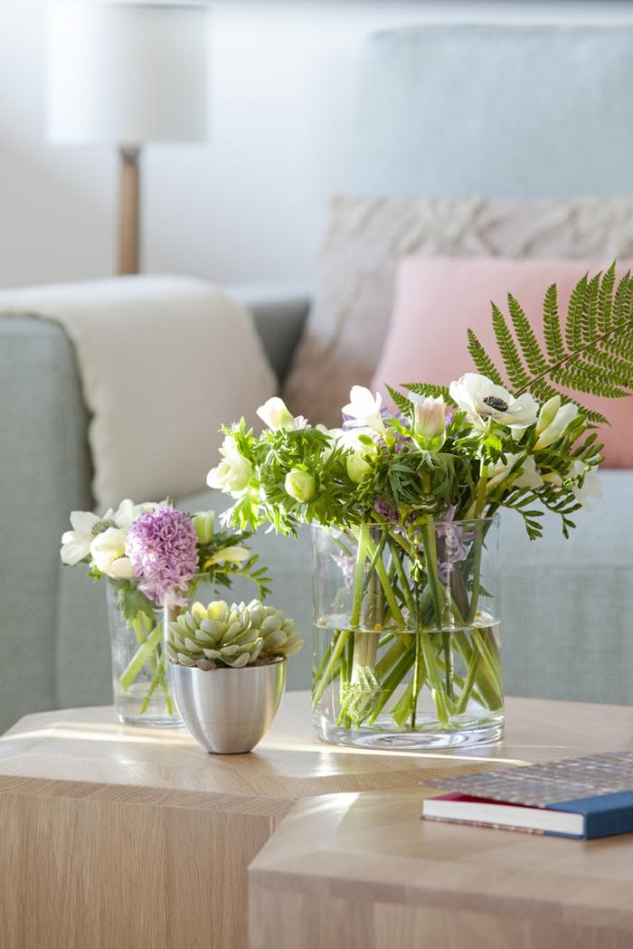 home staging du salon, murs blancs, vase en verre, table en bois clair, journal, bouquet de fleurs fraîches